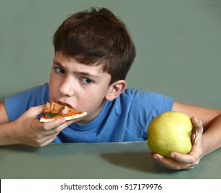 preteen boy eat pizza slice look at the apple close up photo