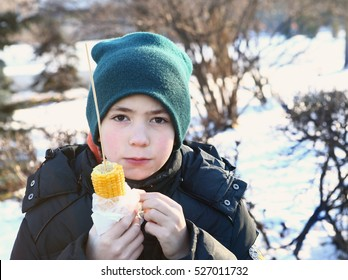 preteen boy eating cob corn on the winter partk backgroun
