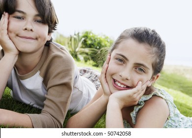 Pre-teen boy and girl reclining, hands on chin on grass