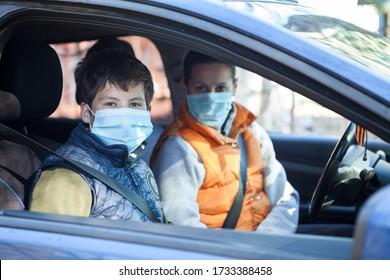Preteen Junge mit seiner Mutter, die im Auto sitzt und medizinische Masken trägt, die sich die Kamera anschauen