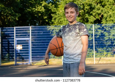 Pre-teen boy holding a basketball on a court in a park