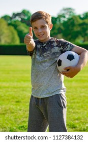 Pre-teen boy holding a football in a park