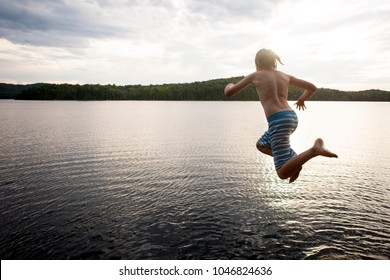 Preteen boy jumping off cliff into a lake.