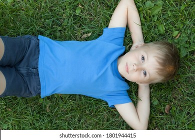 Pre-teen boy lying on back in grass, hands behind head, elevated view.