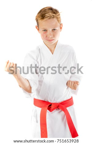 Pre-teen boy in martial arts uniform doing martial arts