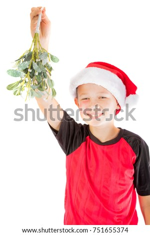 Pre-teen boy with mistletoe wanting a kiss isolated on white background