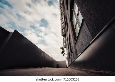 Preteen boy on a street in a big city next to a high-rise building alone. Lifestyle of a serious looking young boy in the city street. jumps from height as assassin