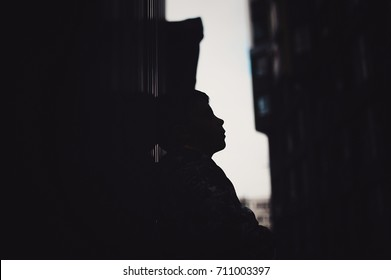 Preteen boy on a street in a big city alone. Lifestyle of a serious looking young boy in the city street. portrait of a young boy on a background of a relief background silhouette view