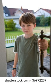 A preteen boy opens a door with his hand on the handle, a confident expression on his face.  Suburban yards and roofs in the background, on a sunny summer day.