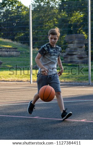 Pre-teen boy playing with a basketball in a park