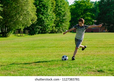 Pre-teen boy playing football in a park
