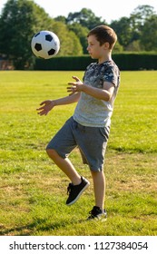 Pre-teen boy playing with a football in a park