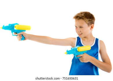 Pre-teen boy playing with water pistols isolated on a white background