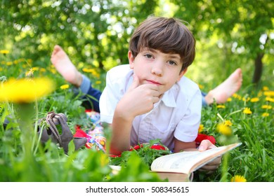 preteen boy reading book in the blossoming spring meadow with dandelions close up portrait