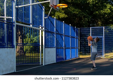 Pre-teen boy shooting basket ball in a park
