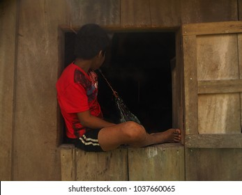 Preteen boy sitting on the window sill of his small rural home on an island off of Bocas del Toro on the Caribbean coast of Panama