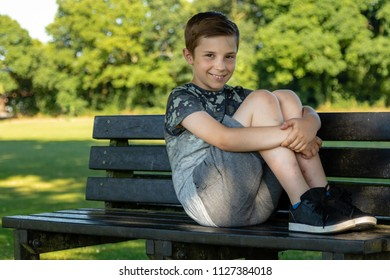 Pre-teen boy sitting outside on a warm summer's day