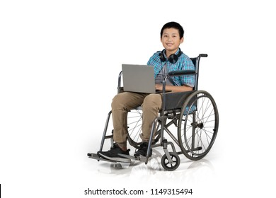 Preteen boy student sitting in a wheelchair while using a laptop in the studio, isolated on white background