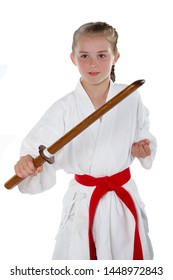 Pre-teen caucasian girl wearing a karate uniform performing a sword kata with a wooden training sword