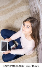 Preteen child playing on ipad sitting on a carpet at home. beautiful girl with tablet. Girl listening to music on headphones