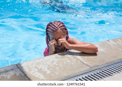 Preteen European girl crying and wiping water from her eyes when swimming in pool