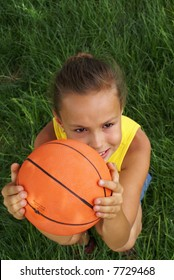Preteen girl with basketball on grass background