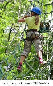 Preteen girl is climbing on the rope net at the ropes course. She is photographed on the high tree in the green forest.