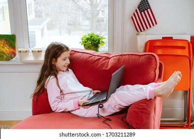 Preteen girl enjoyes homeschooling in comfy pajama and cozy sofa chair. Remote education, virus protection, social distancing  and lockdown concept. household items at the back