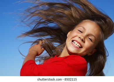 Preteen girl flipping hair on blue sky background