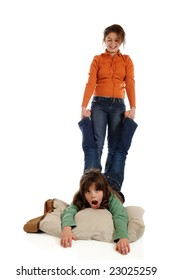 A preteen girl happily pulling her elementary sisters by her feet.  Isolated on white.