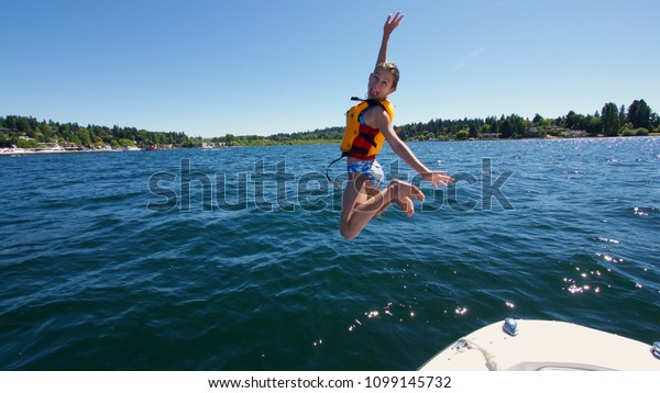 A pre-teen girl having fun jumps from a boat into Lake Washington, located in Seattle, Washington on a sunny, summer afternoon.