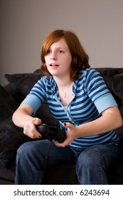 Preteen girl playing an exciting video game at home.