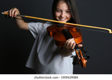 Preteen girl playing violin on black background, focus on hand