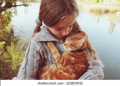 Preteen girl with red cat in her arms. Photo toned style Instagram filters.