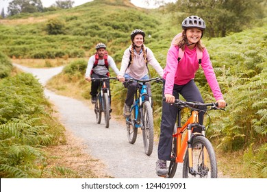 Pre-teen girl riding mountain bike with her parents during a family camping trip, close up