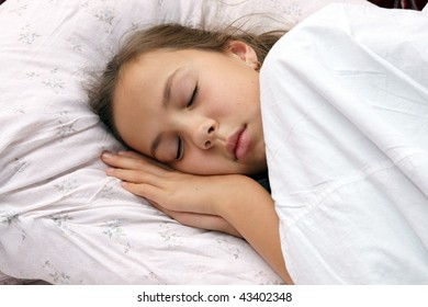 Preteen girl sleeps in bed