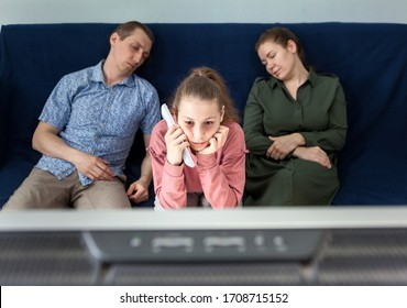 Pre-teen girl with sleepy look watching television at night during her parents sleeping on couch, family at home