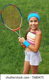 Preteen girl with tennis racket on grass background