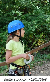 Preteen girl is wearing on the outfit for rope parkour. She is photographed in the summer forest.
