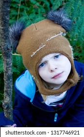 Preteen girl wearing a playful winter hat holds a walking stick and  scowls with a confused expression with lush ferns in the background. Photo taken in Madison, WI, USA