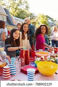 Pre-teen girls smiling to camera at a block party food table