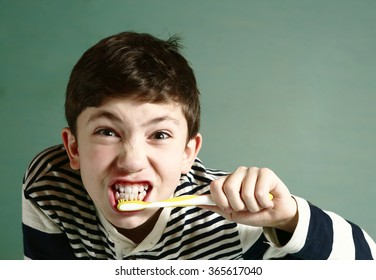 preteen handsome boy brush his strong white healthy teeth grimacing close up portrait