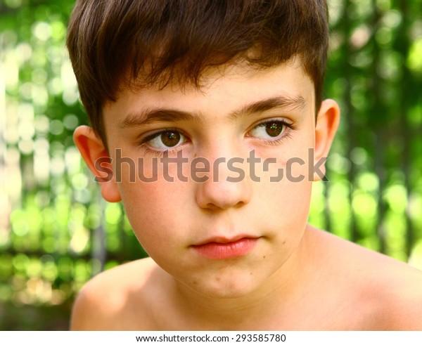 preteen handsome boy close up outdoor portrait on the summer garden fence background