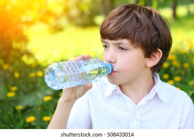 preteen handsome boy drink water. Boy drinking water from the bottle on the outdoors summer park green background.