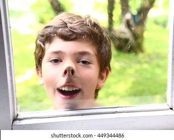 preteen handsome boy pressed nose against the window glass close up smiling portrait