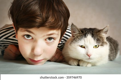 preteen handsome boy with siberian tom cat close up portrait