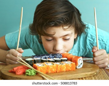 preteen handsome boy smell sushi roll set and stick hungry