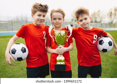Preteen happy soccer players after final game. Boys holding golden cup and soccer balls. Sports portrait of three happy football players. Football youth junior team posing outdoor and facing camera