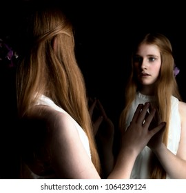 preteen with red hair looking into mirror