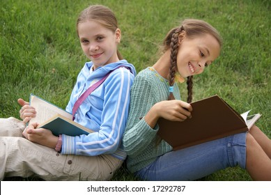 Preteen school girls reading books on green grass background outdoors